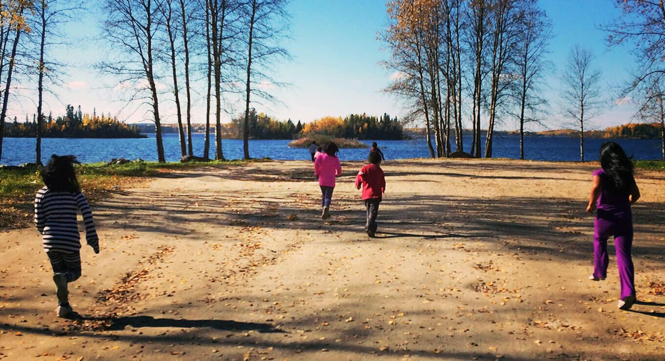 Children running on a road with a lake in the background