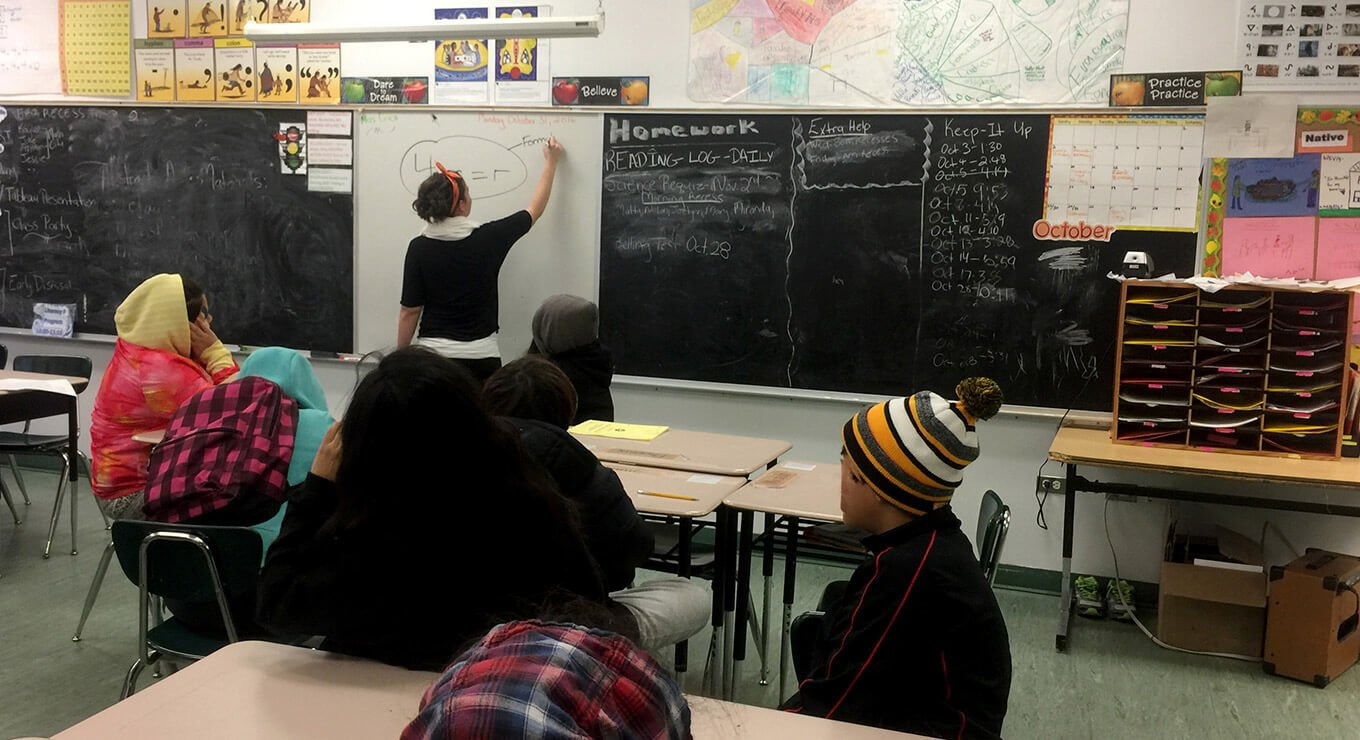A teacher writing on a whiteboard with students watching