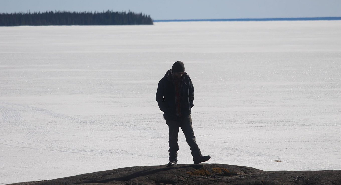 A man standing in front of a frozen lake