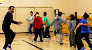 A teacher and students playing in a gymnasium