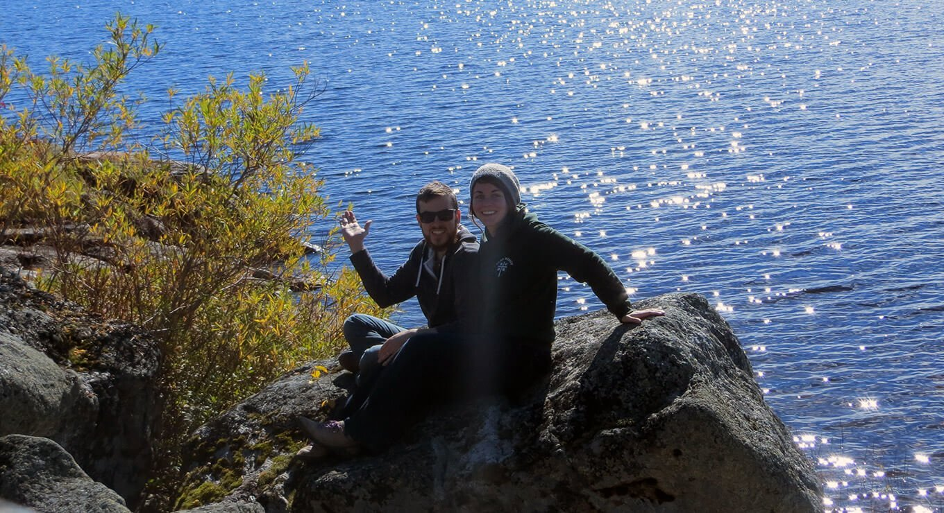 Two people sitting on a rock in front of water