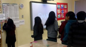 Students writing on chart paper, next to a Smart board