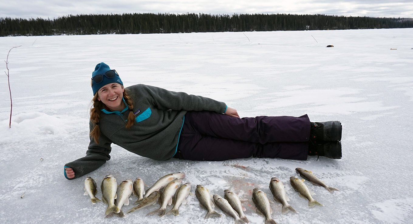 A woman laying on her side on a frozen lake, behind a row of fish