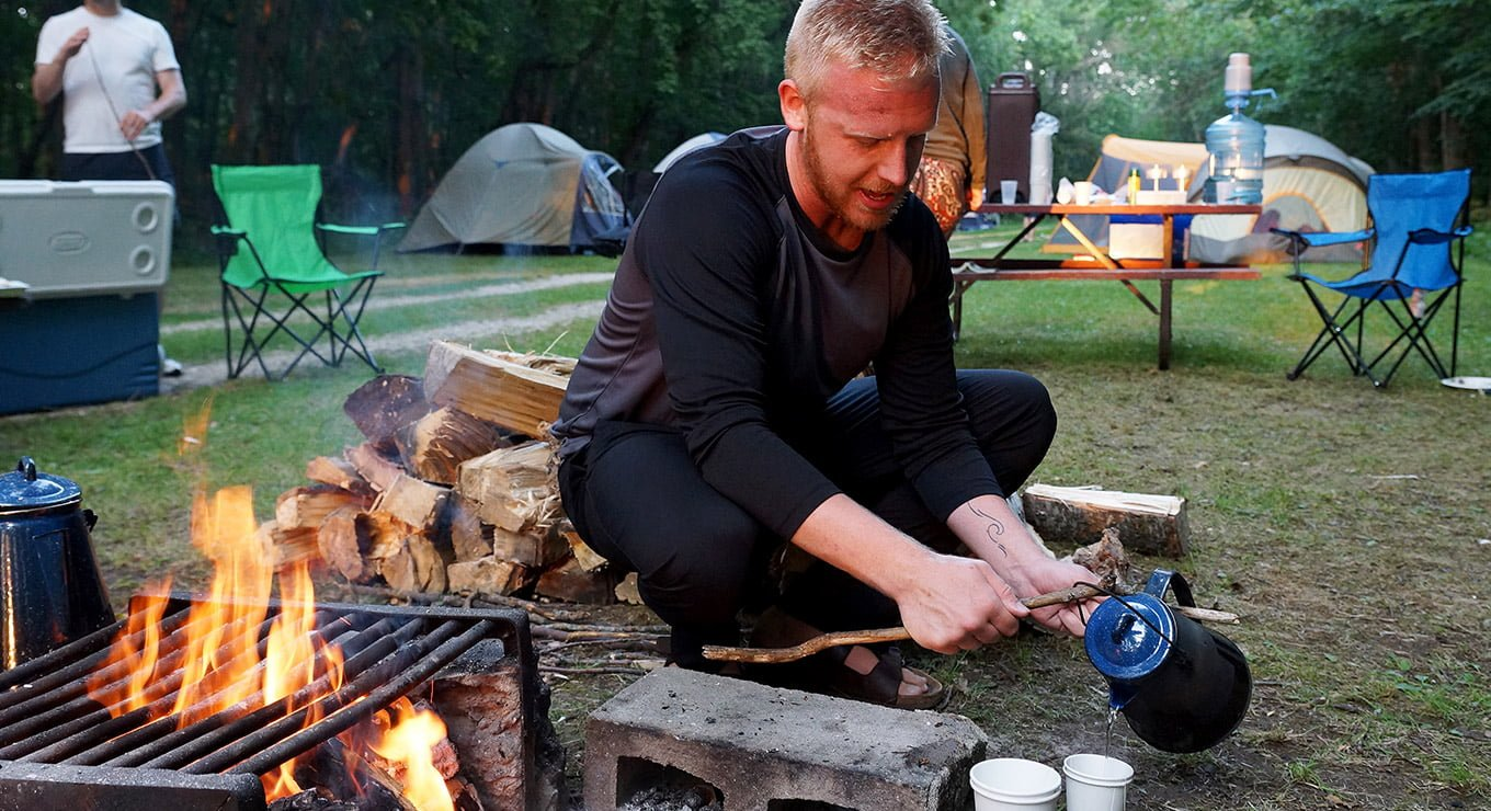 A man by a campfire pouring water out of a jug into paper cups