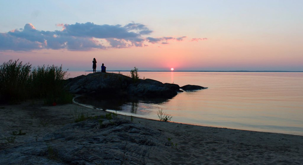 Two people on a big rock on the shore of a lake with a sunset in the background