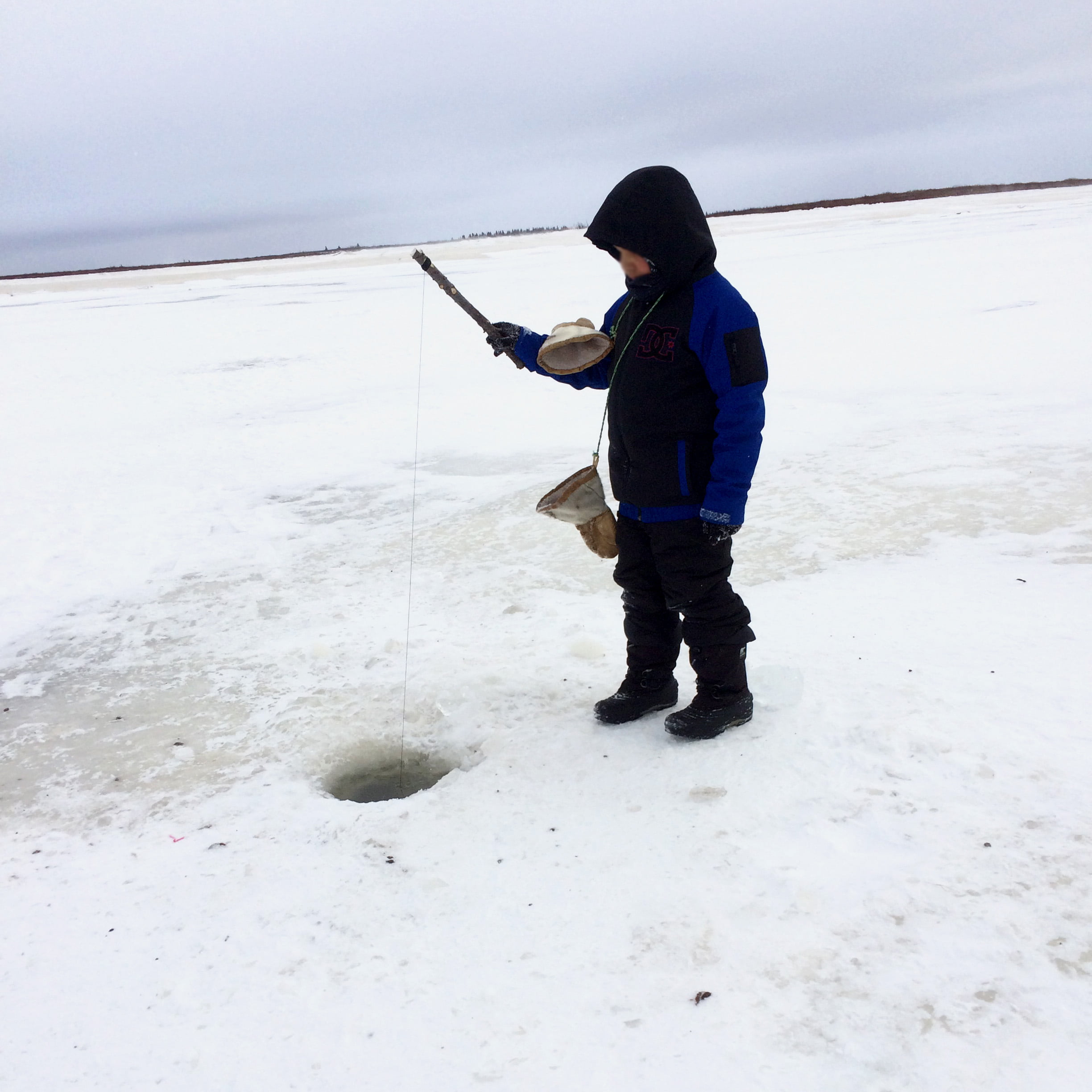 Student ice fishing in Fort Severn First Nation