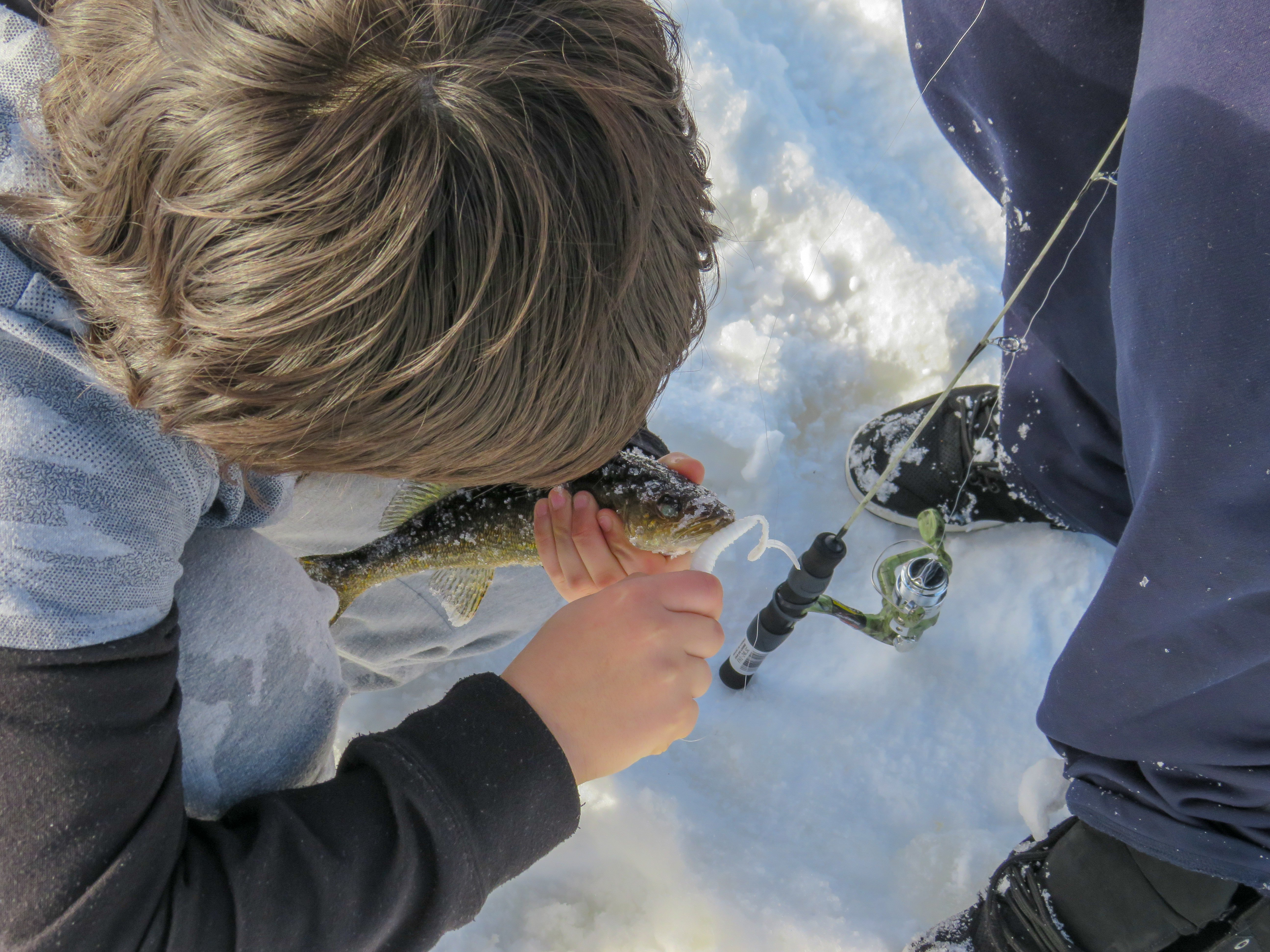 A student unhooking a fish caught ice fishing in Cat Lake First Nation