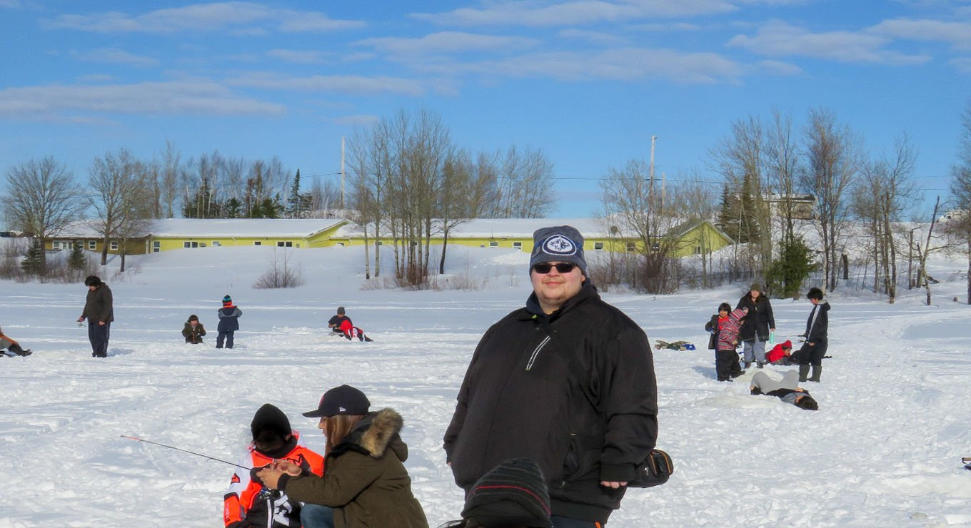 Matt Fairley ice fishing with students in Cat Lake First Nation