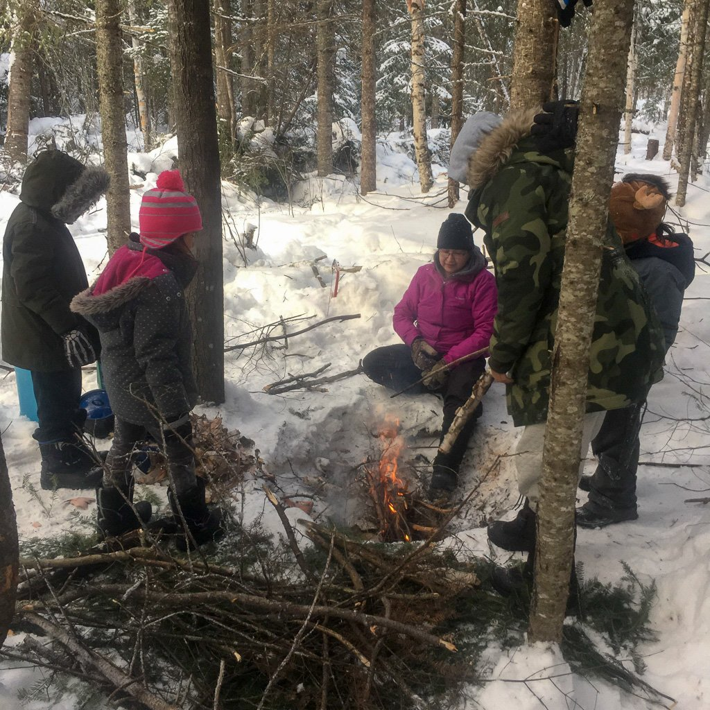 An Elder teaches students what kind of kindling they should use to build a fire