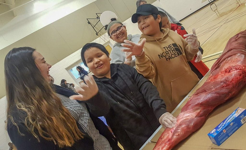 Jenn and her students have fun as they learn to cut moose