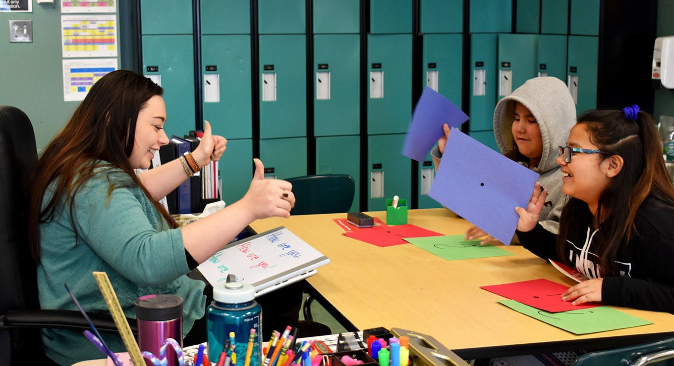 Teach For Canada teacher Jenn Elwell working with two students