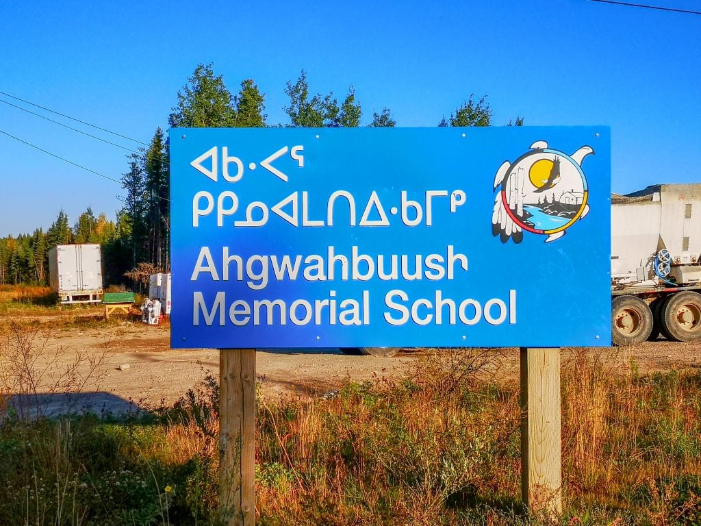 A bilingual sign outside of Ahgwahbuush Memorial School