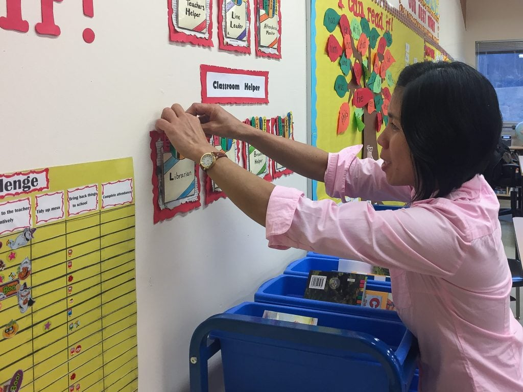 Doreen prepares a new bulletin board in her grade 2 class