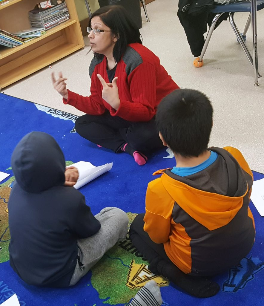 Jaya teaching her students sitting on a mat in her classroom