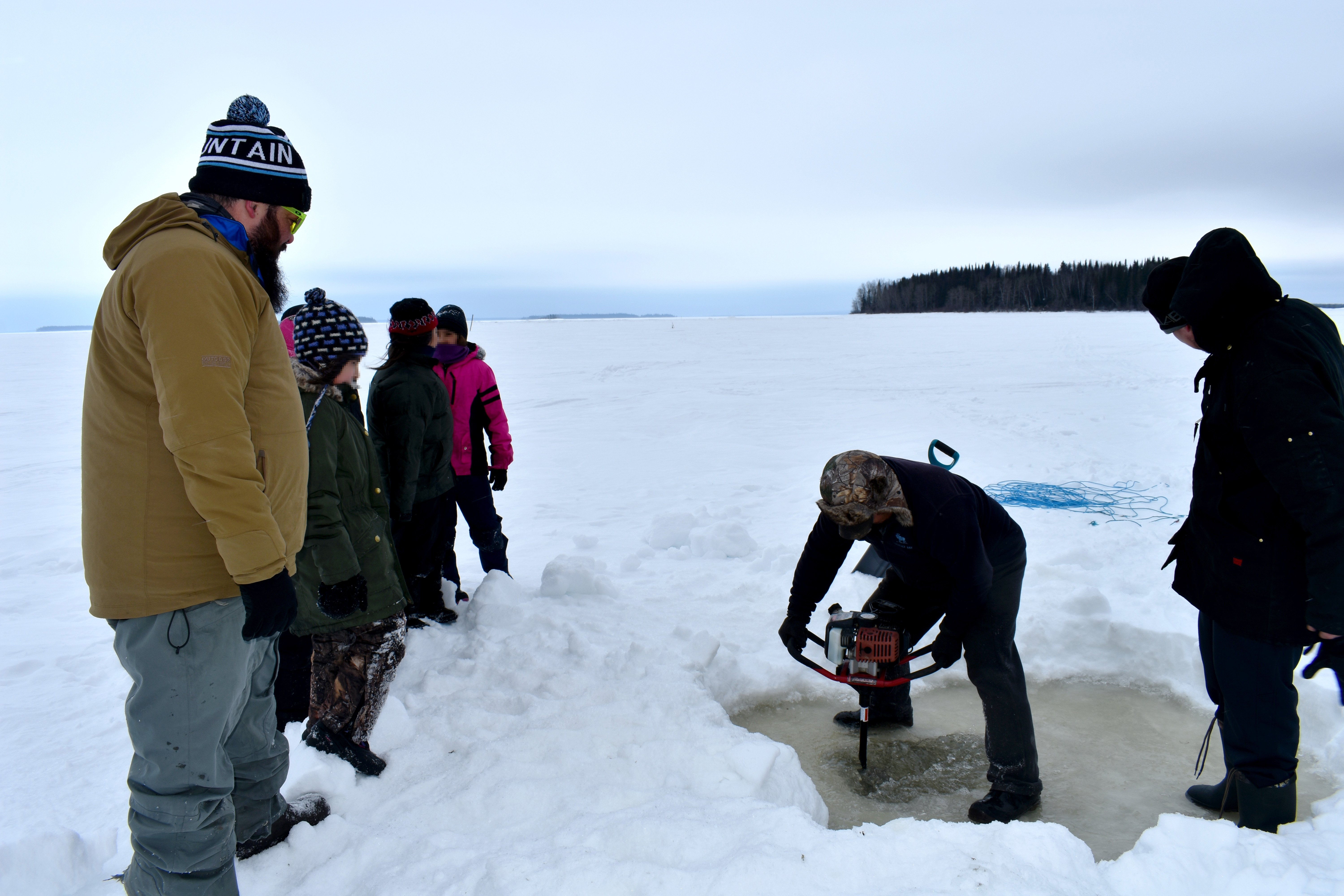 A teacher and his students watch as a hole is drilled into the ice