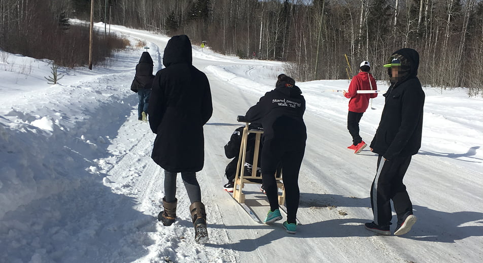 Youth push a kicksled down a snowy road