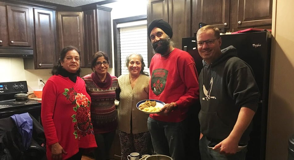 Five people stand around a potluck dinner in a kitchen