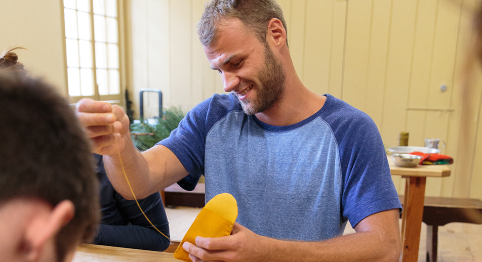 Brenton sewing a mocassin