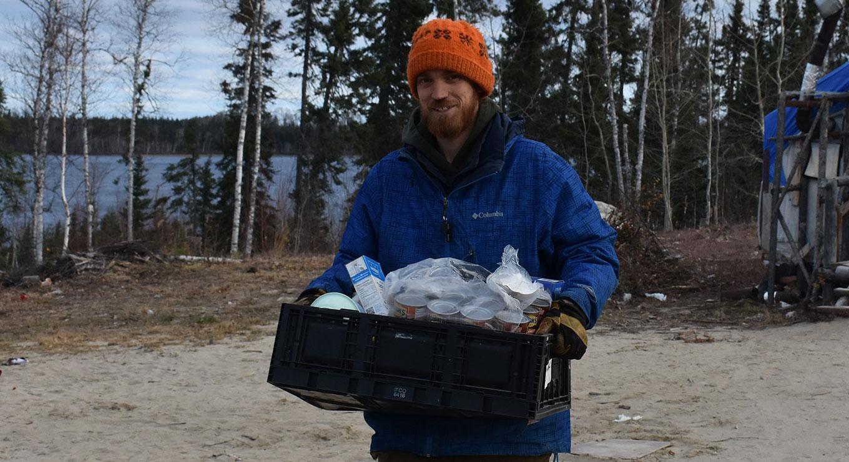 A teacher carries supplies by a lake
