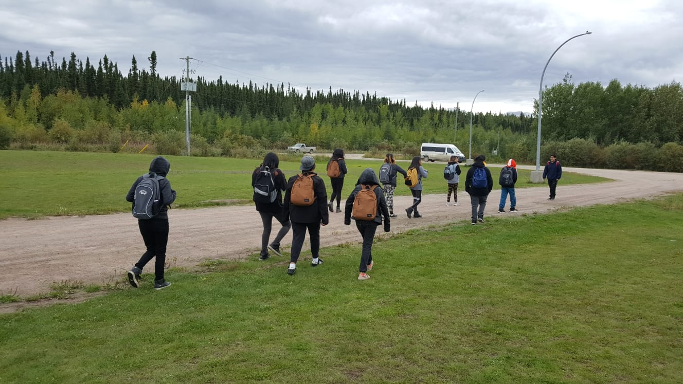 Students walk down a road wtih backpacks on