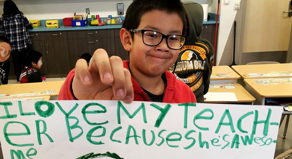 "A student in Fort Severn First Nation holds a sign that reads: ""I love my teacher because she is awesome"""
