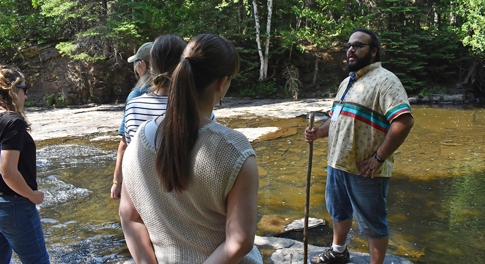 Bryan Bellefeulle facilitates a session on land-based learning with Teach For Canada teachers by a creek